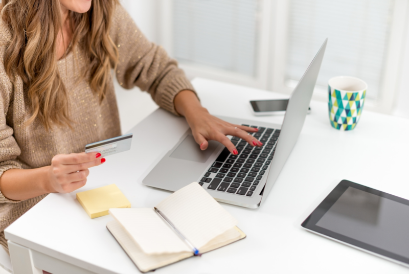 woman sitting at a table typing with her left hand on laptop and holding credit card in her right hand